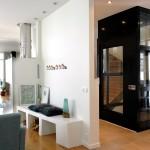 schwarzer Plattformlift aus Glas im Eigenheim