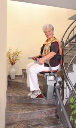 Frau auf Treppenlift für Kurventreppen